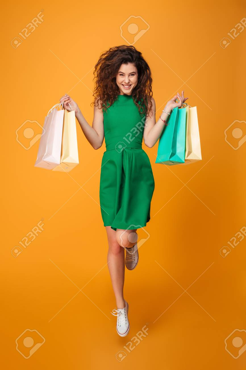 Image of happy young woman standing isolated over yellow background. Looking camera holding shopping bags. - 97254764