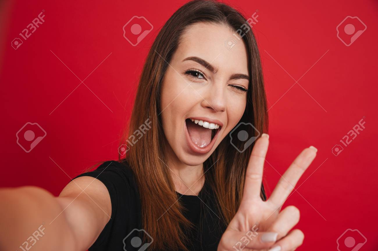Cute woman 20s in black t-shirt having fun and taking selfie with gesturing peace sign isolated over red background - 97800706