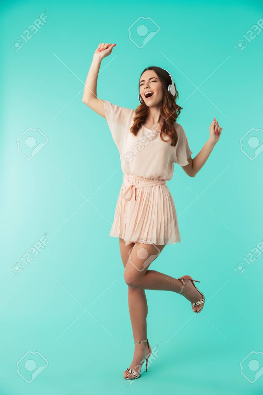 Full length portrait of a happy young girl in dress listening to music with headphones and dancing isolated over blue background - 99548177