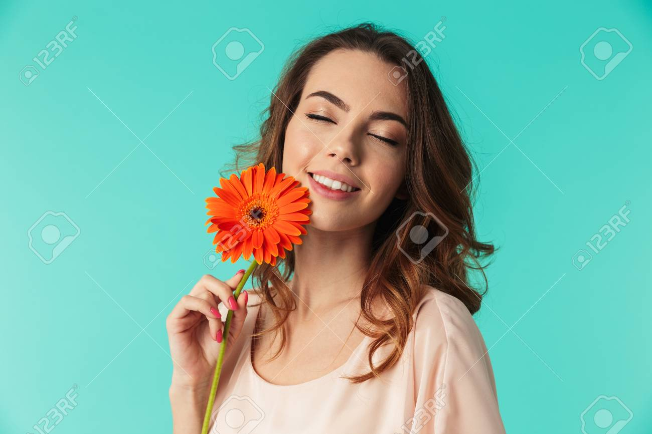 Portrait of a pretty young girl in dress holding gerbera flower isolated  over blue background Stock c0f729e04