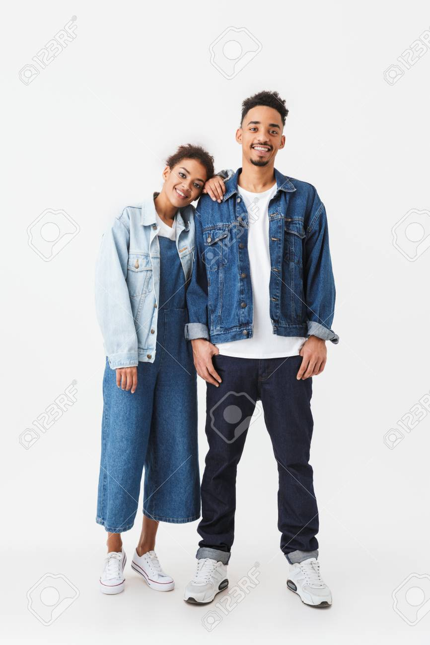 224b310646e Full length image of Smiling african couple in denim shirts standing  together and looking at the