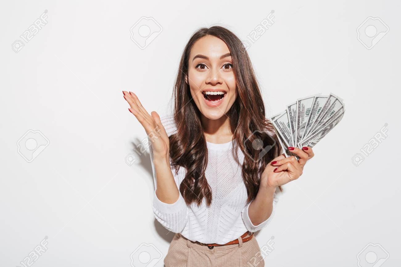 Portrait of an excited young asian businesswoman showing money banknotes and celebrating isolated over white background - 101486727