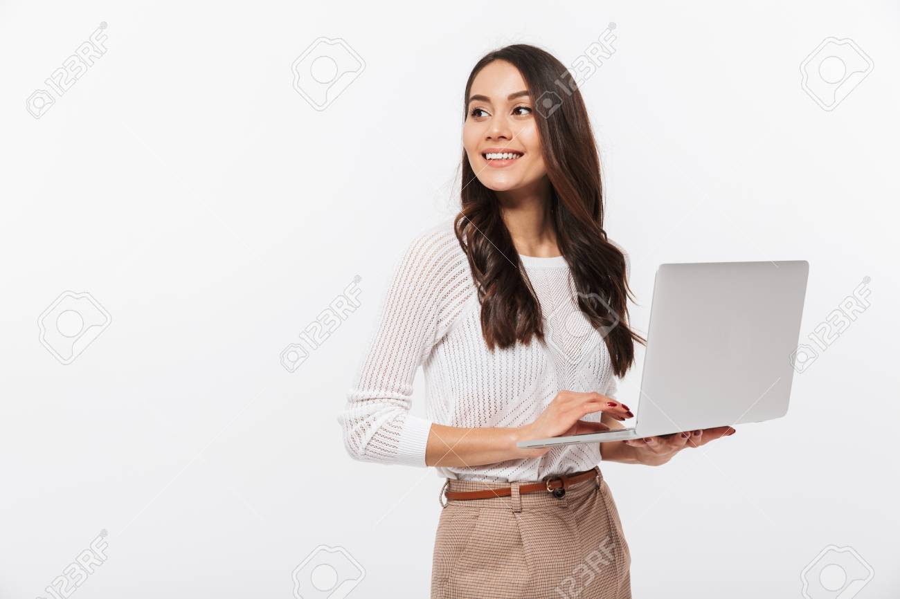 Portrait of a happy asian businesswoman holding laptop computer iand looking away solated over white background - 101487367
