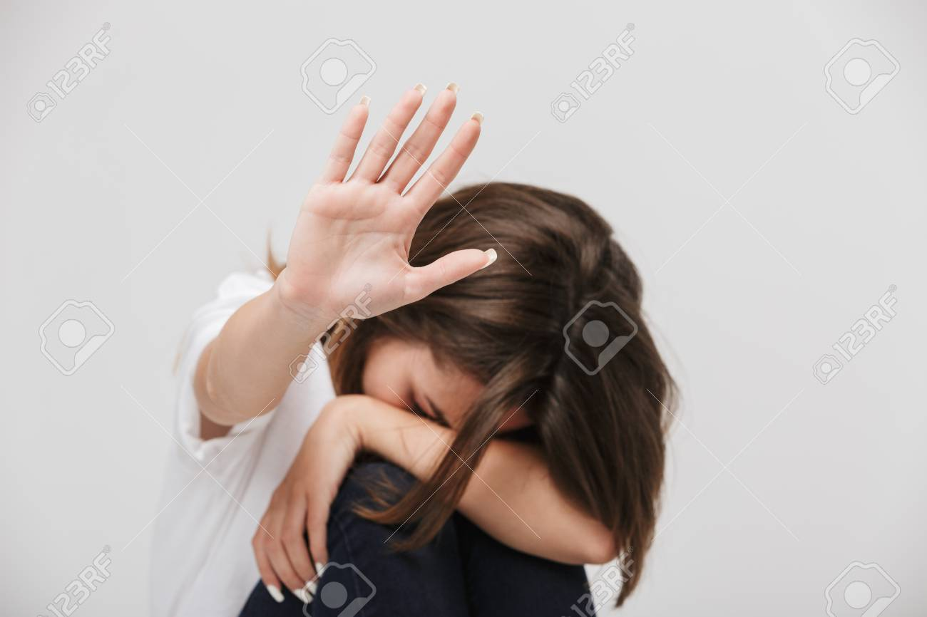 Photo of a disabled young girl sitting isolated over white background wall covering herself with hands showing stop gesture. - 104562453