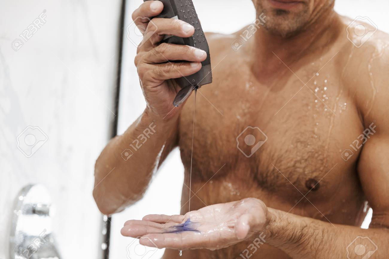 Close Up Of A Sexy Naked Man Putting Shower Gel From A Bottle While Having A