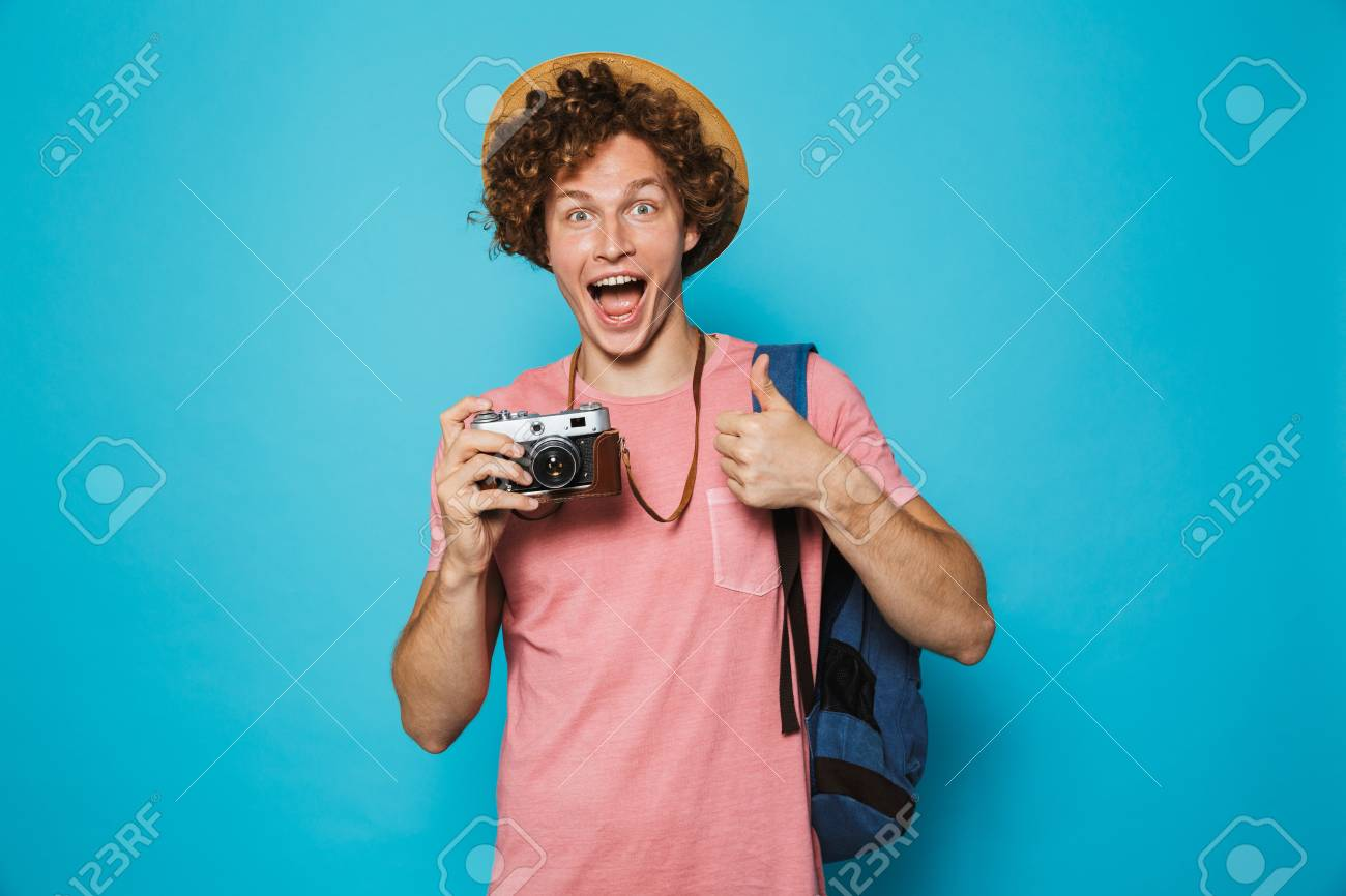 Photo of joyous traveler boy 18-20 with curly hair wearing backpack