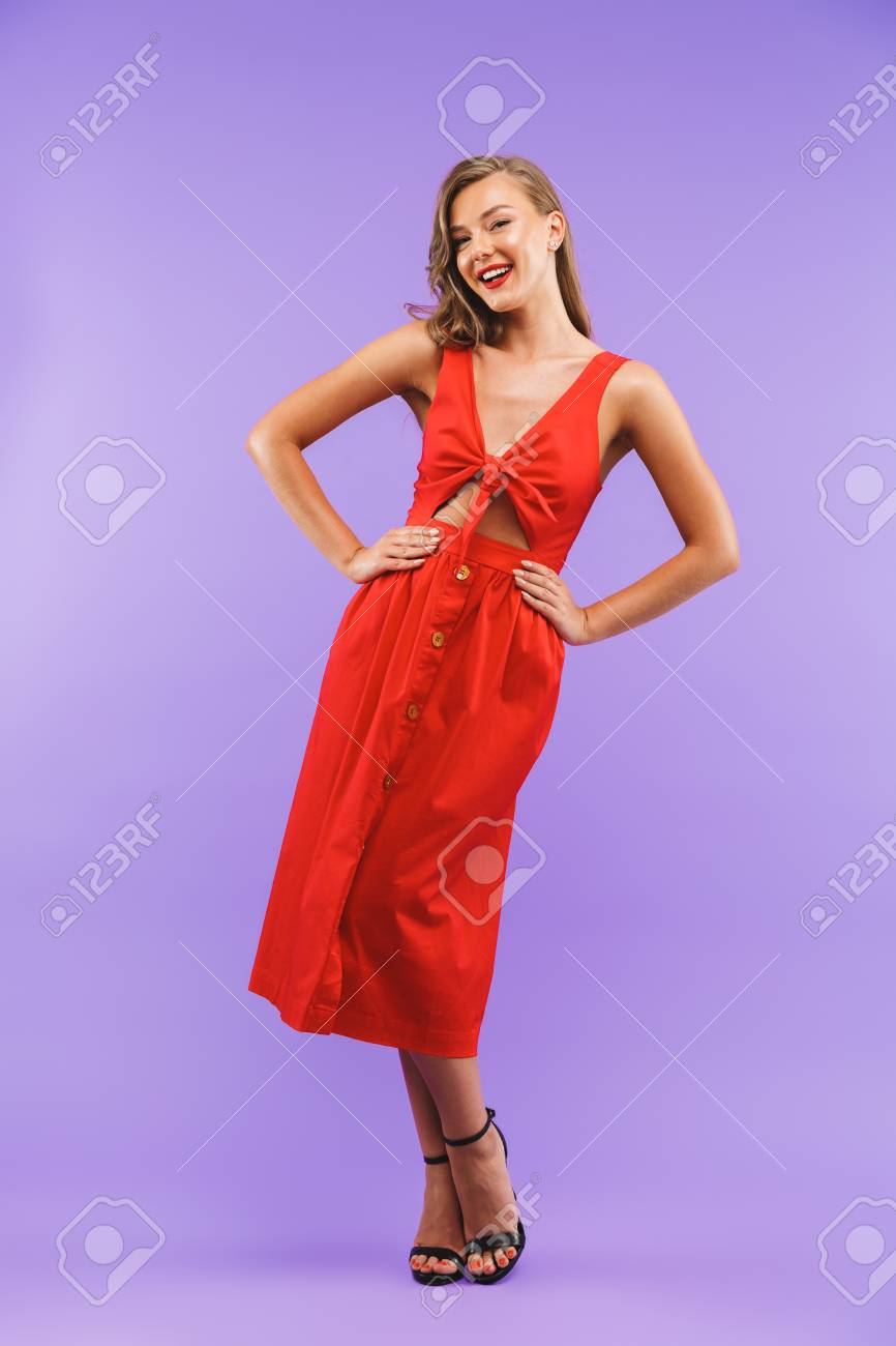 Full length portrait of caucasian cute woman 20s wearing red dress smiling at camera standing isolated over violet background - 107764287