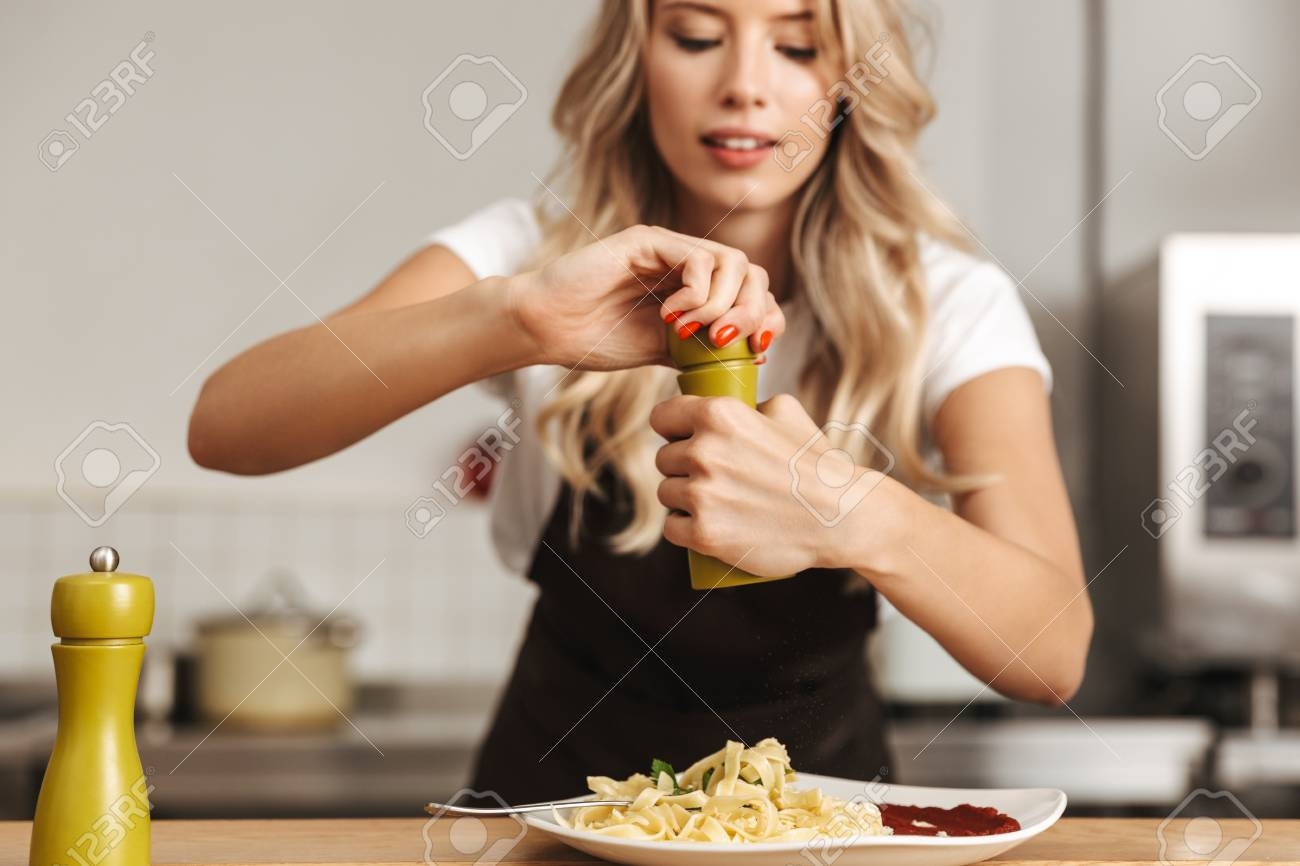 Pretty young woman chef putting salt in a pasta - 109093548