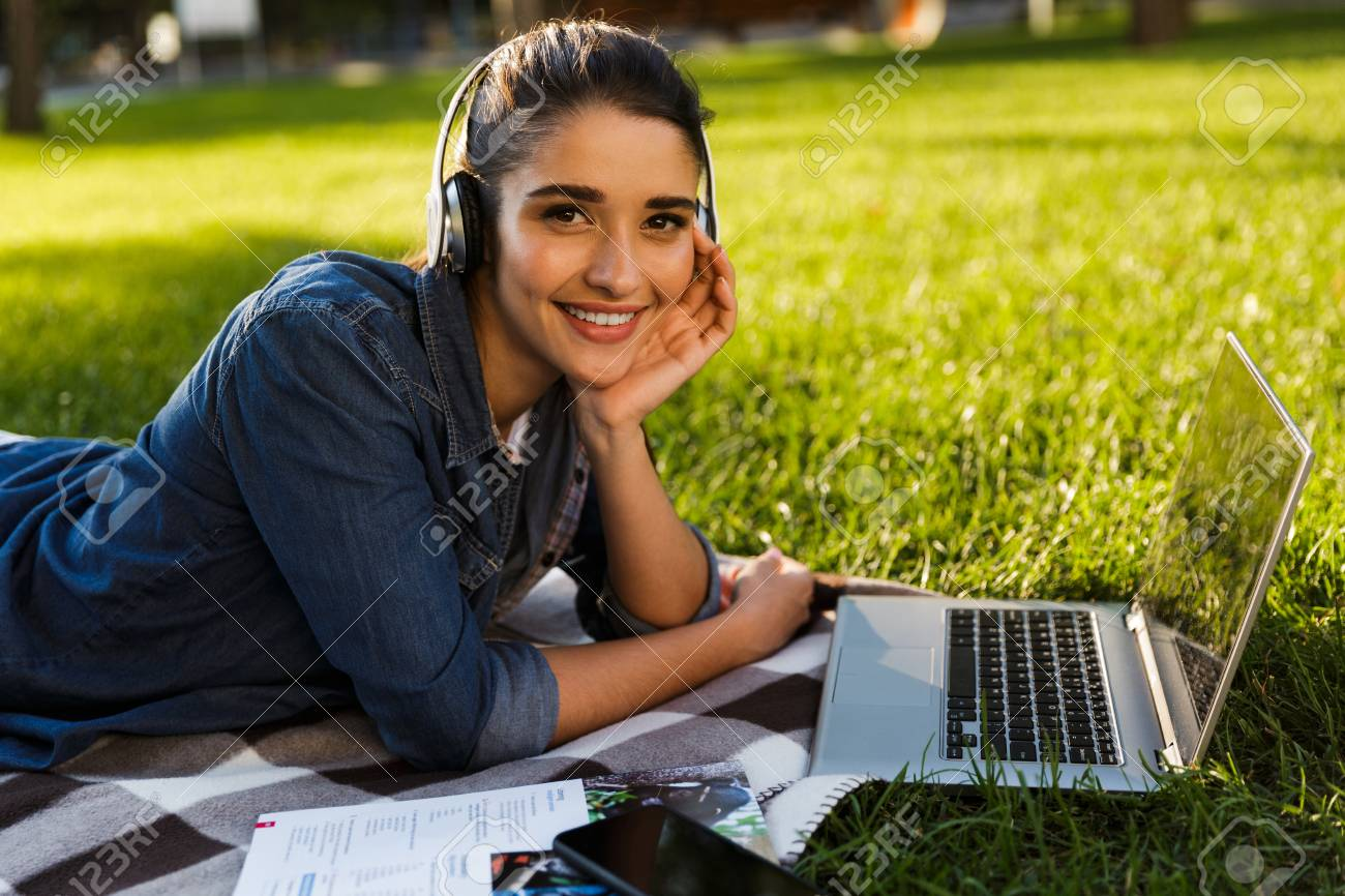 Image of amazing beautiful young woman student in the park using laptop computer listening music with headphones. - 110648901