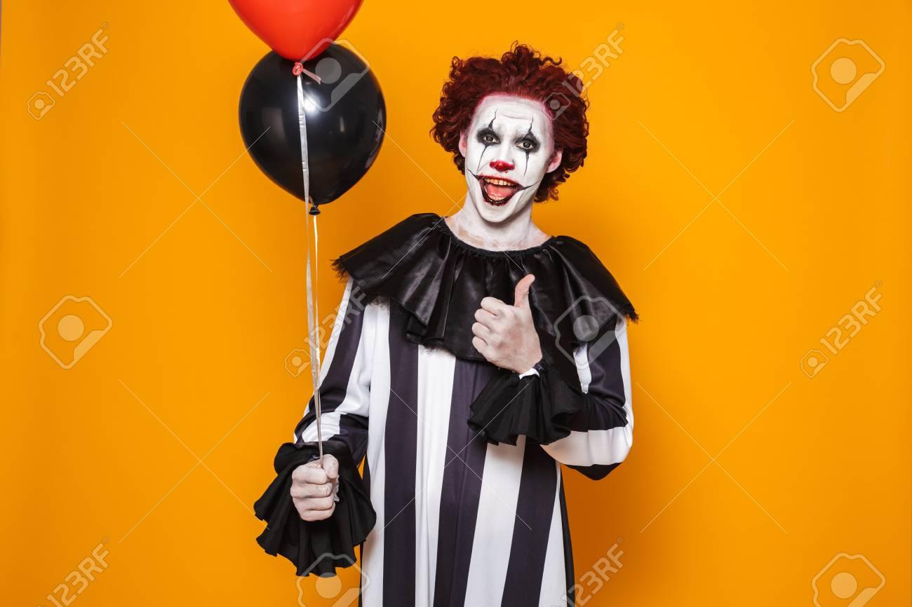 Scary Clown Halloween Costume.Angry Man Dressed In Scary Clown Halloween Costume Holding Balloons