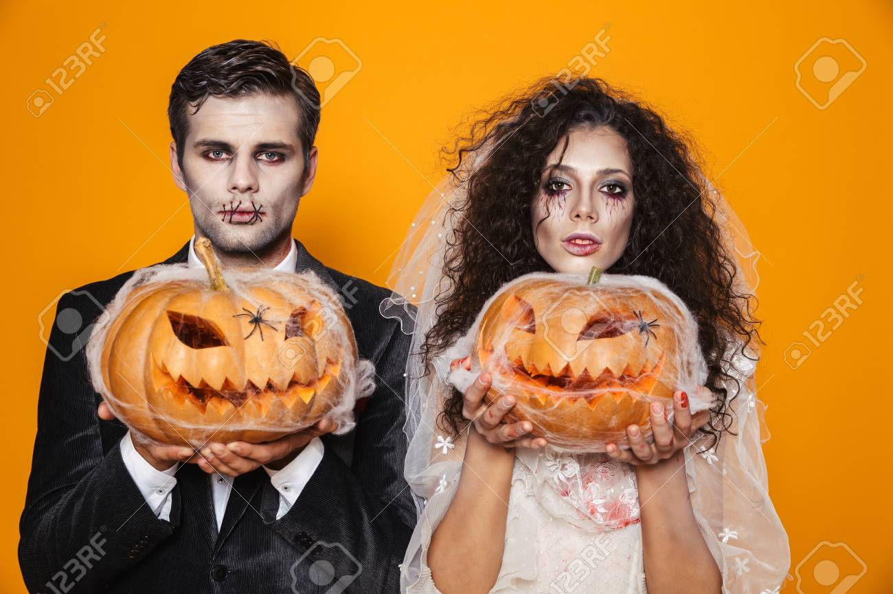 Photo of scary zombie couple bridegroom and bride wearing outfit and halloween makeup holding carved pumpkin isolated over yellow background - 112483885