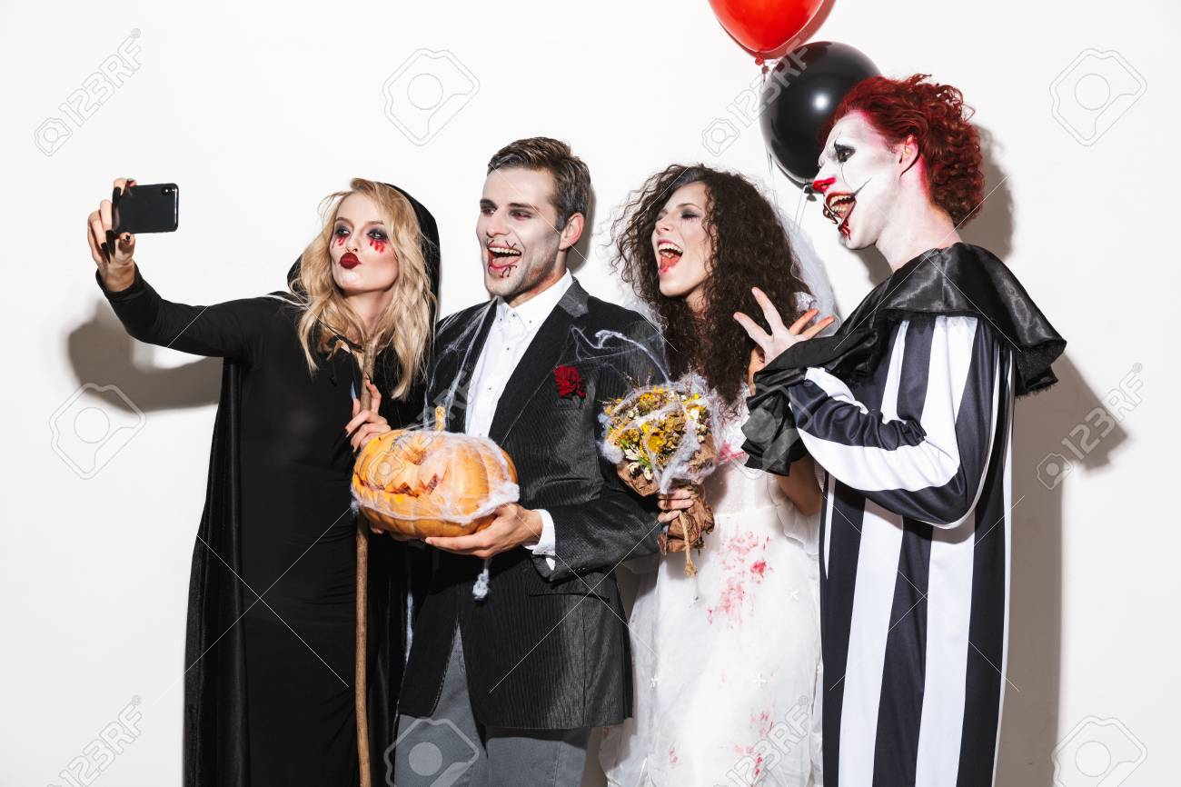 Halloween Group Costumes Scary.Group Of Smiling Friends Dressed In Scary Costumes Celebrating
