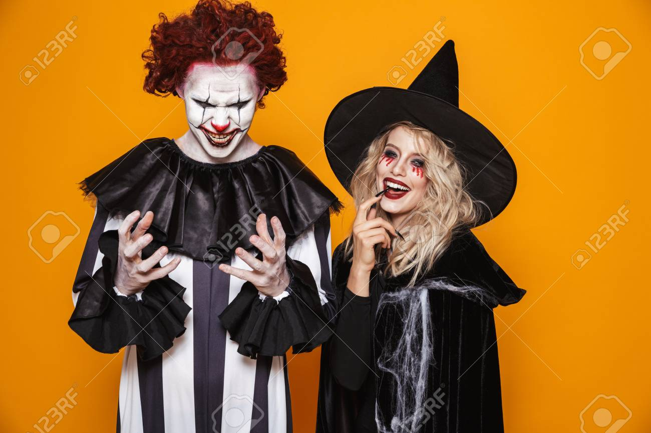 Image of witch woman and clown man wearing black costume and halloween makeup smiling at camera isolated over yellow background - 112484090