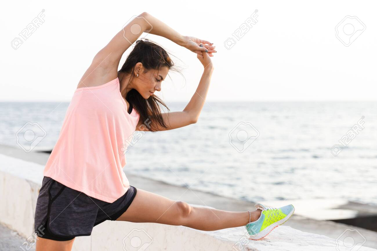 Photo of athletic woman 20s in tracksuit stretching her body during workout at seaside - 140860865