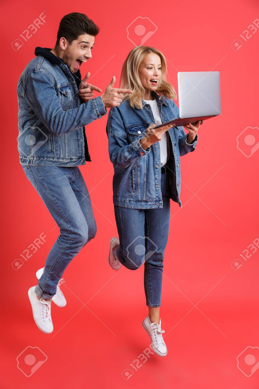 Full length portrait of an excited young couple dressed in denim jackets jumping together isolated over red background, looking at laptop computer, pointing finger - 112727912