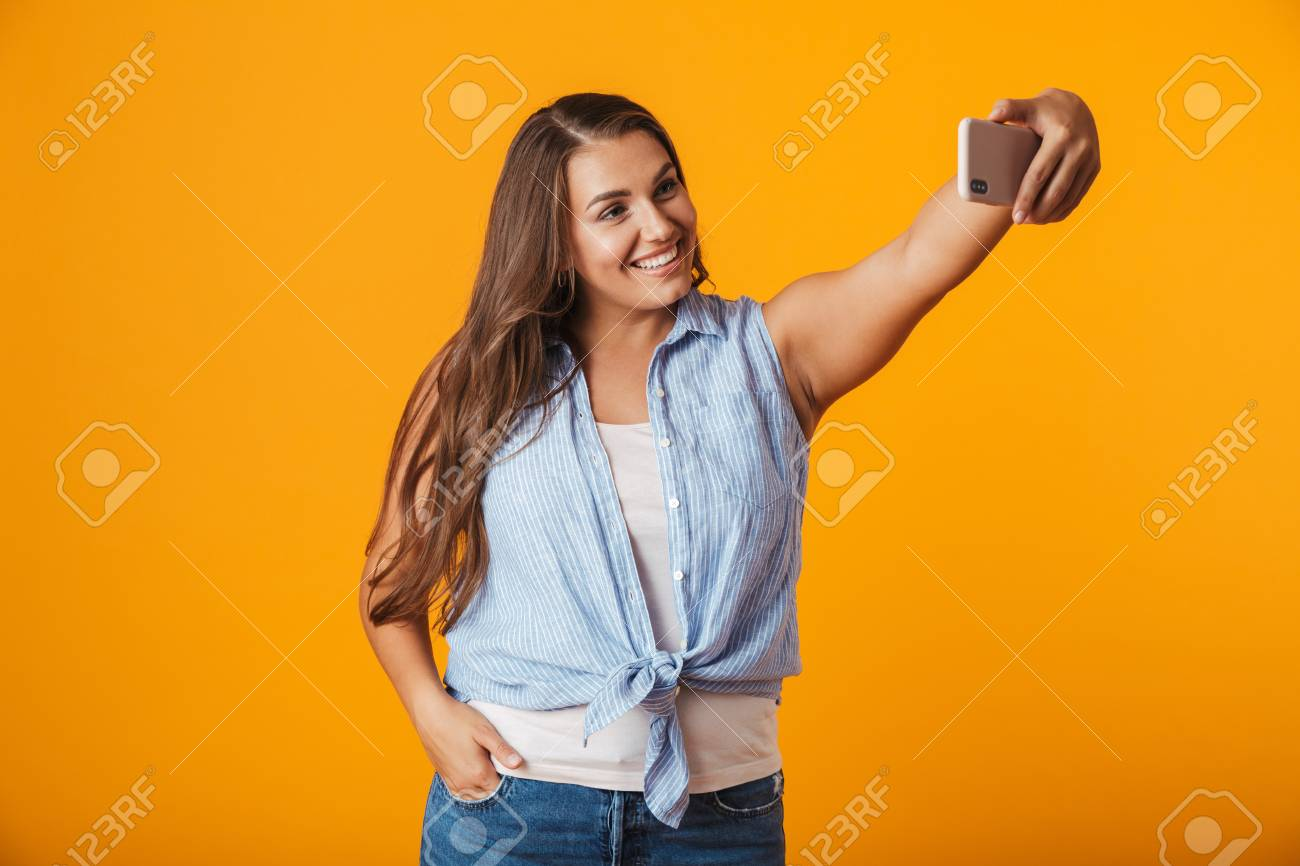 Cheerful young woman standing isolated over yellow background, taking a selfie with outsretched hand - 113601856