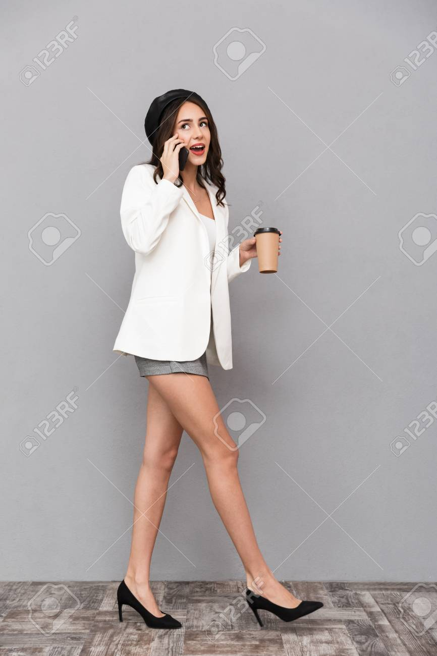 Full length portrait of a cheerful young woman dressed in mini skirt and jacket over gray background, holding cup of coffee, talking on mobile phone, walking - 115344589