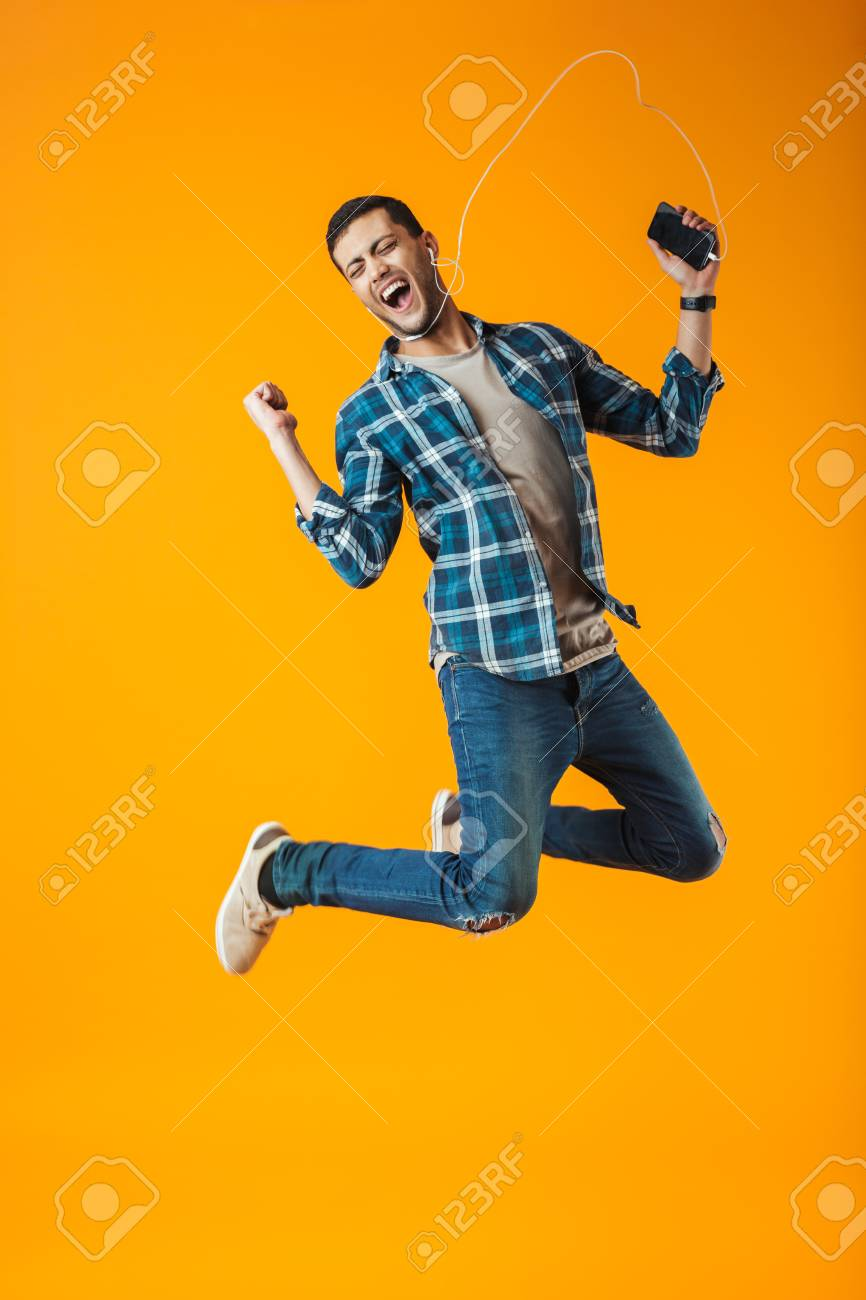 Excited young man wearing plaid shirt jumping isolated over orange background, listening to music with earphones and mobile phone - 115886437