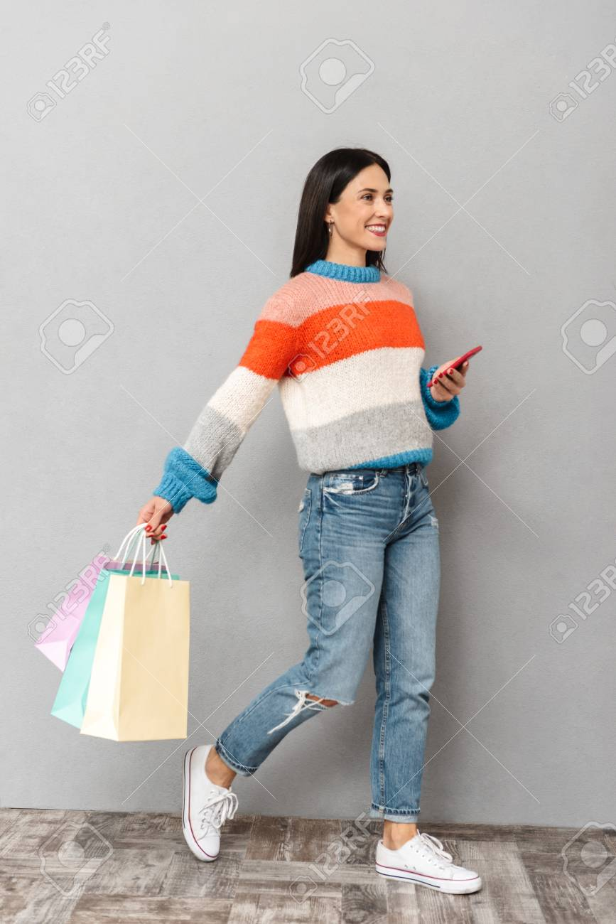 Portrait of joyful woman 30s walking with colorful paper shopping bags and cell phone in hands isolated over gray background - 117379917