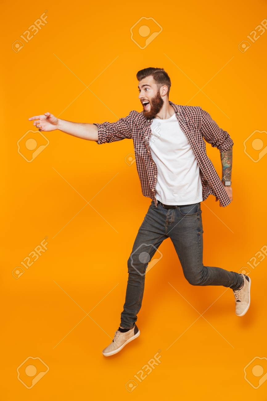 Full length portrait of a cheerful young man wearing casual clothes running away - 117906728