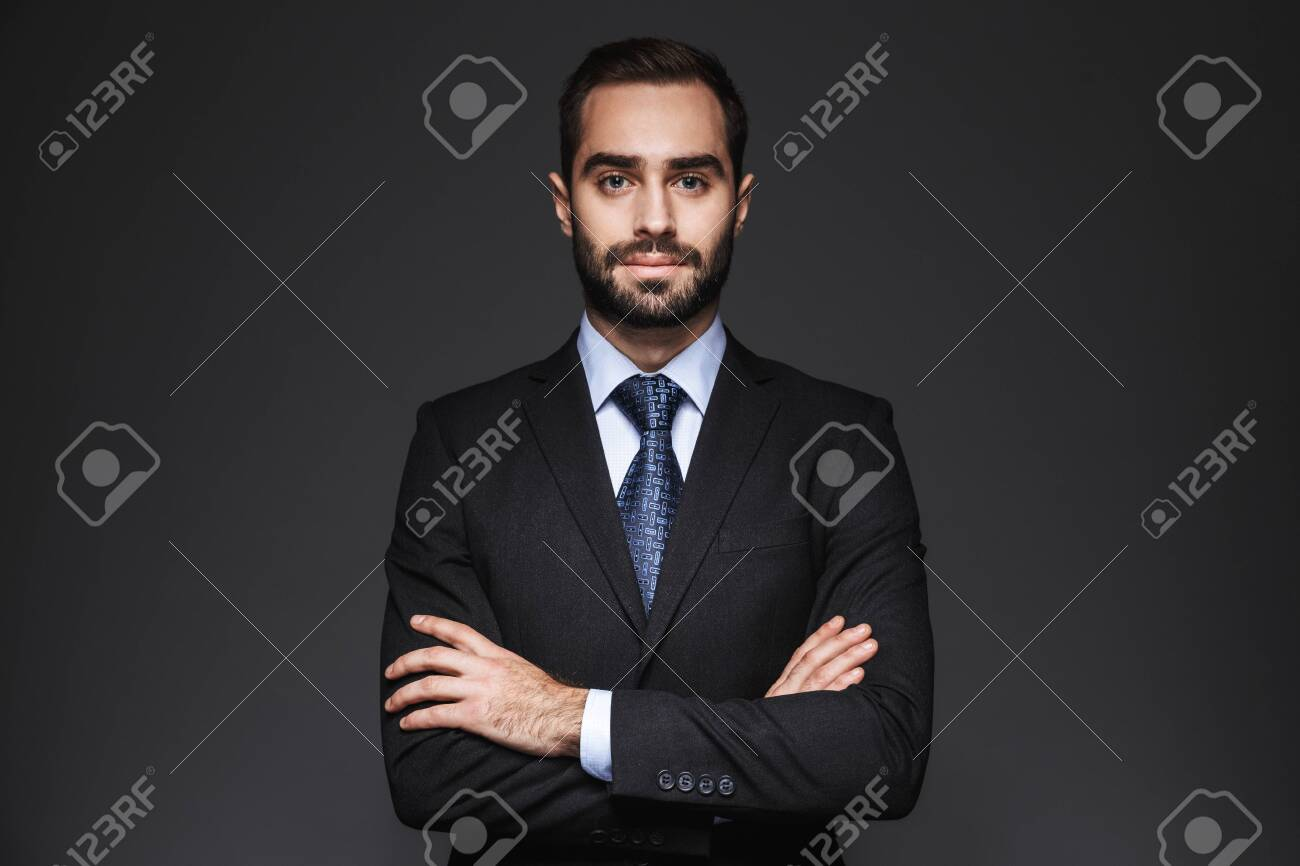 Portrait of a confident handsome businessman wearing suit isolated over black background, arms folded - 119013910