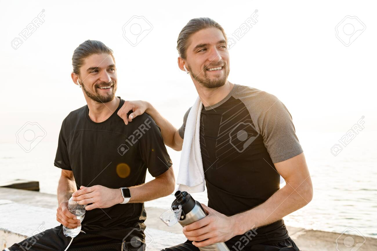 Two twin brothers doing exercises at the beach together - 120354176
