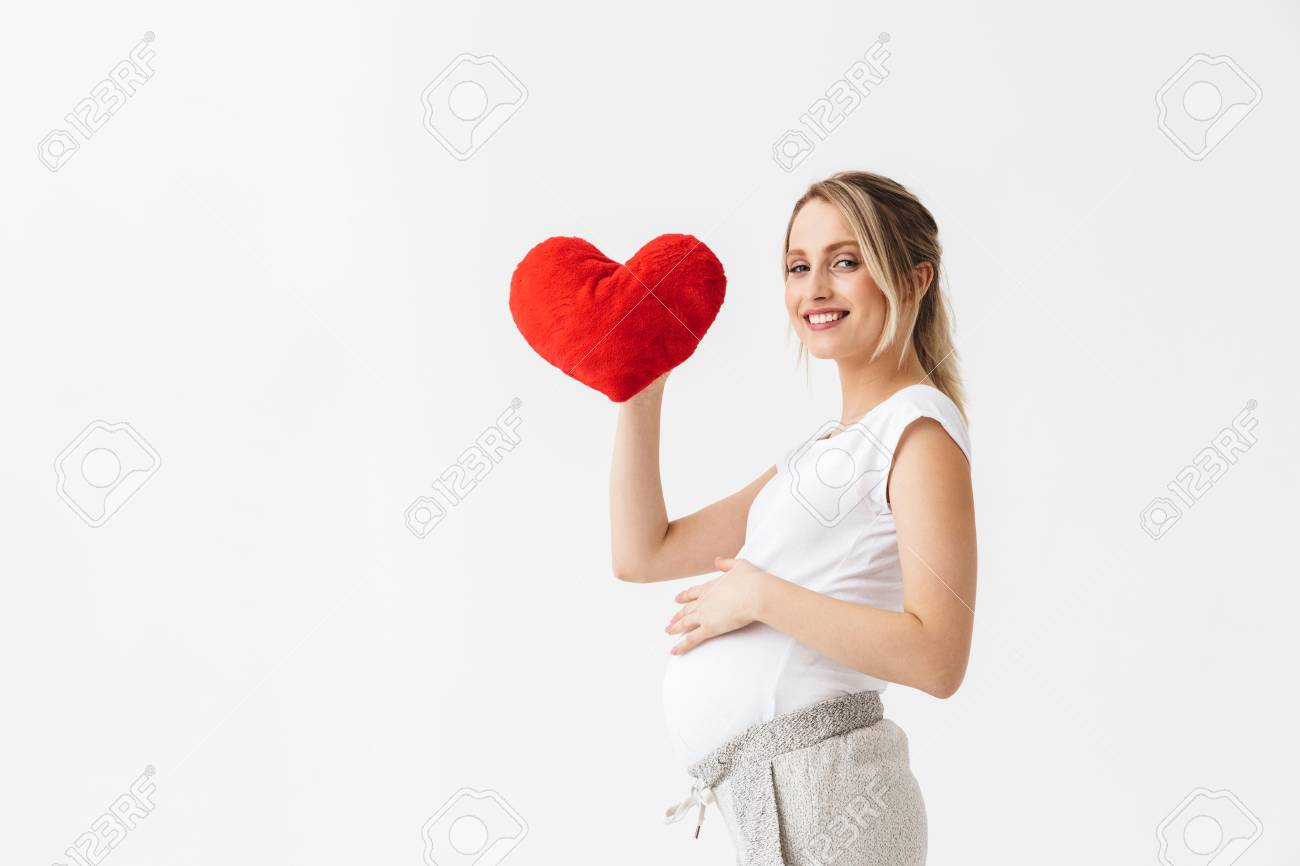 Beautiful young pregnant woman standing isolated over white background, holding heart - 120563976