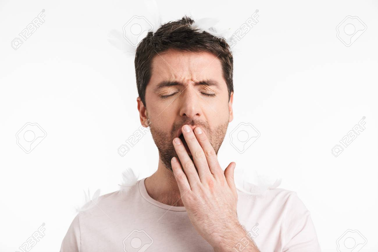 Image of sleepy man 30s with bristle in casual t-shirt yawning while standing under falling feathers isolated over white background - 121189800