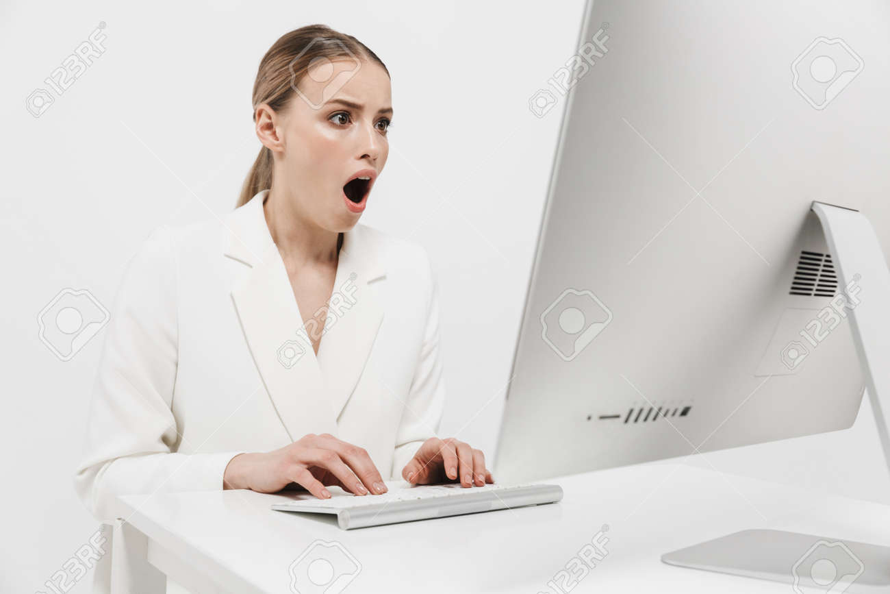 Image of a shocked beautiful amazing woman sitting isolated over white wall background using pc computer. - 122704455