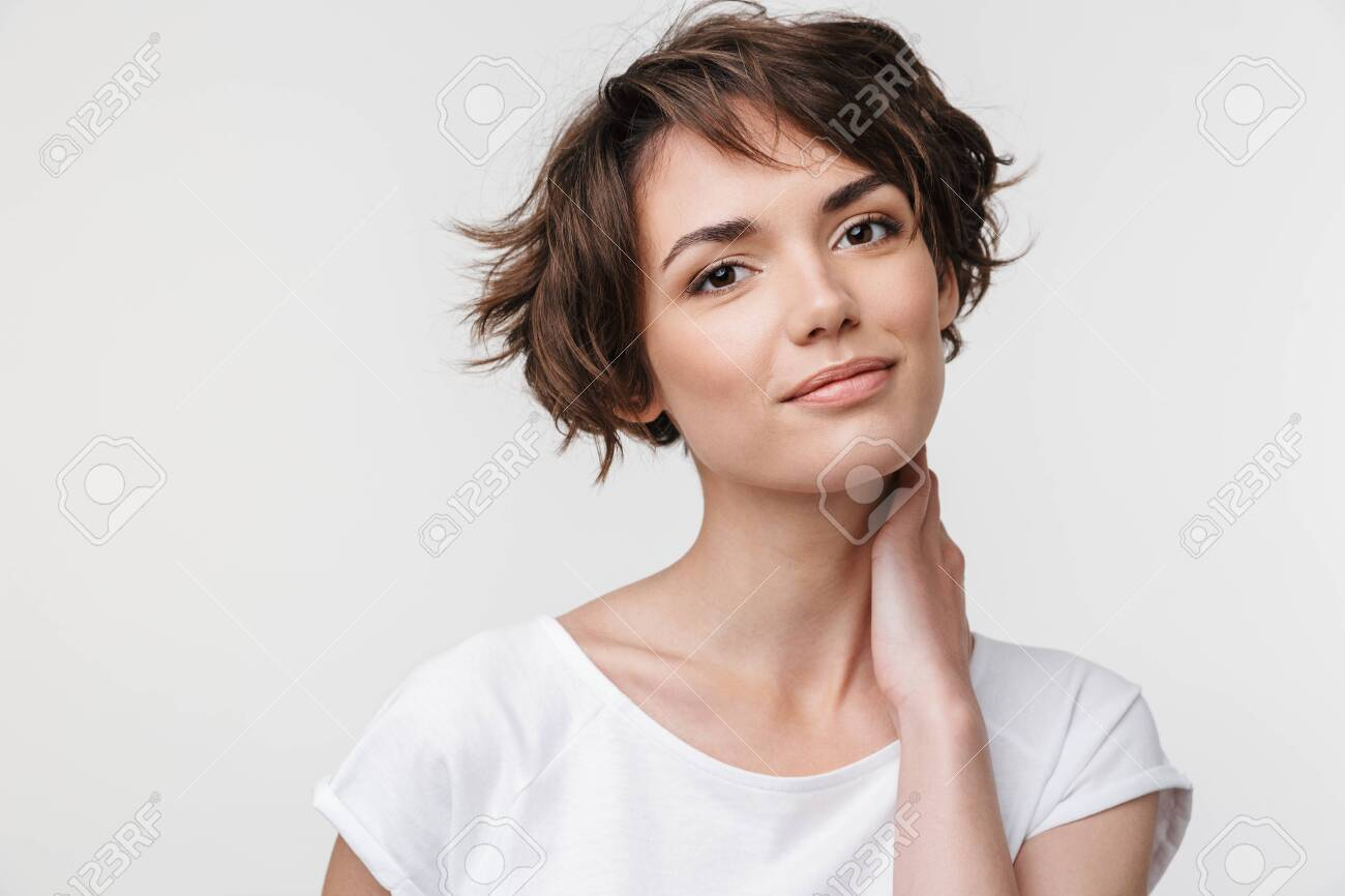 Portrait of pretty woman with short brown hair in basic t-shirt looking at camera while standing isolated over white background - 124482671