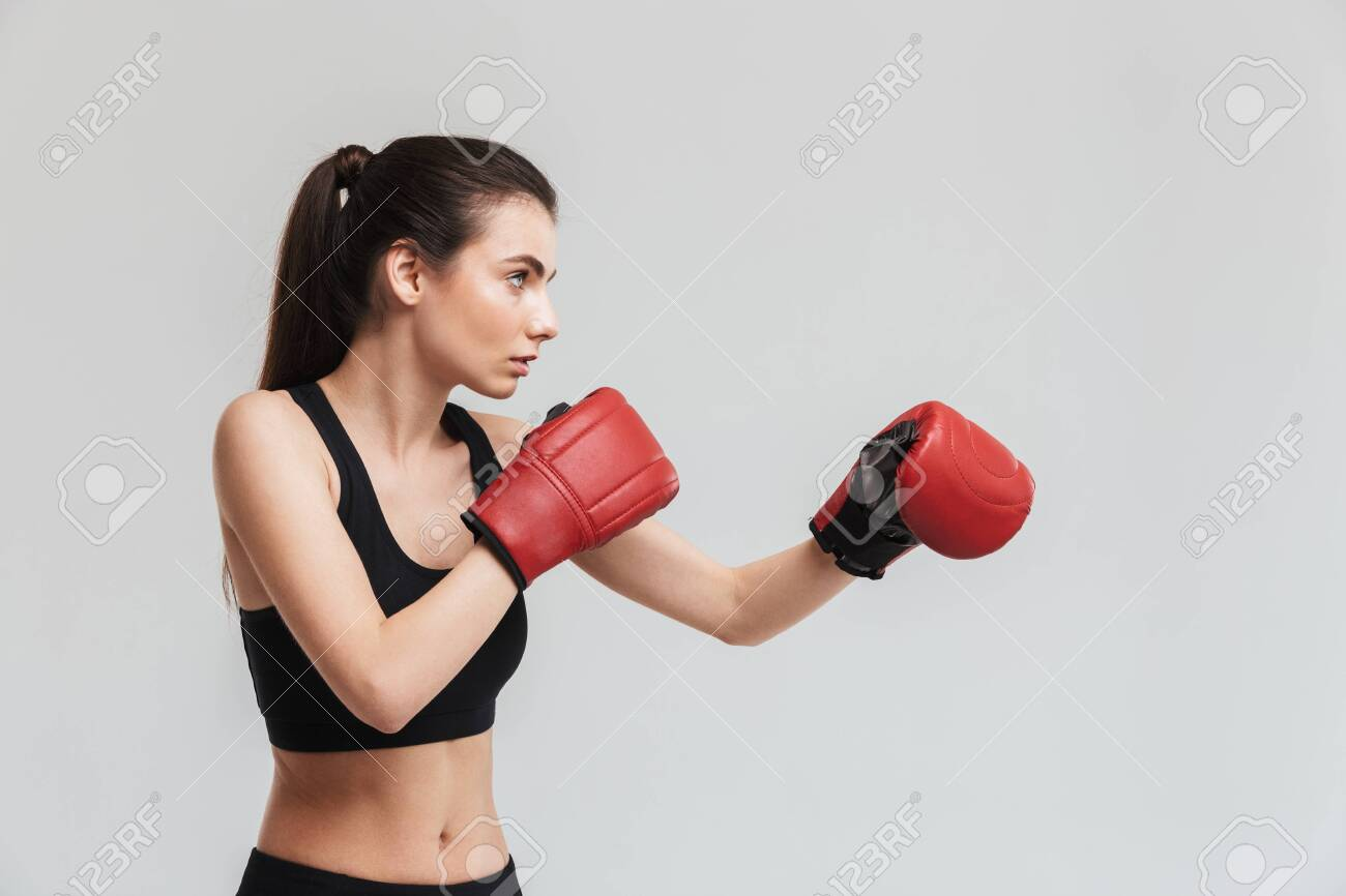 Image of a beautiful young sport fitness woman boxer isolated over grey wall background make exercises in gloves. - 126595493