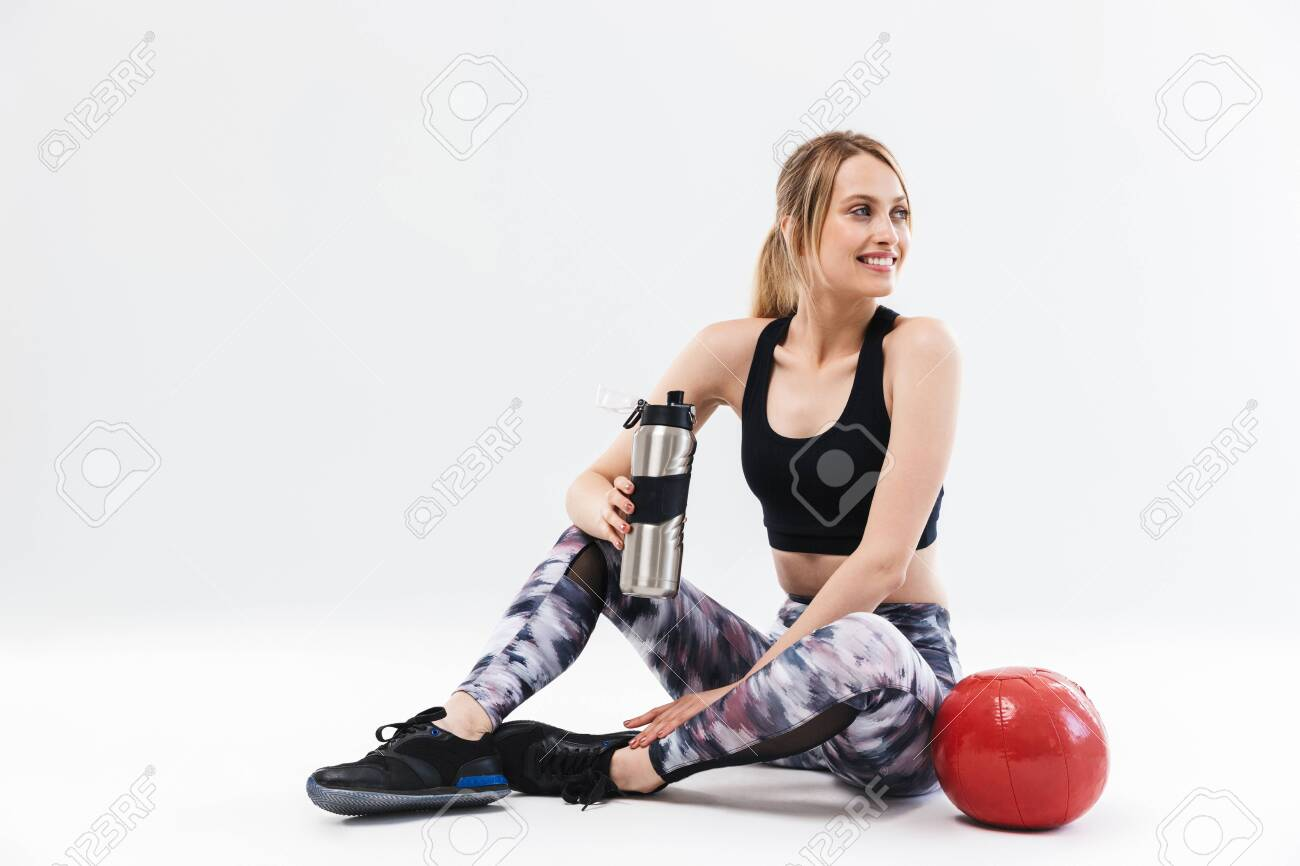 Image of european blond woman 20s dressed in sportswear working out and doing exercises with fitness ball during aerobics isolated over white wall - 126777298