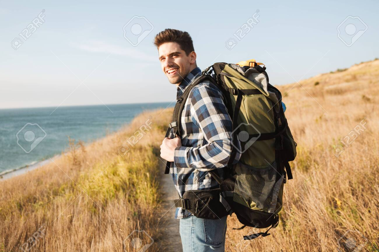 Attractive Smiling Young Man Carrying Backpack, Hiking Stock Photo, Picture And Royalty Free Image. Image 126788053.