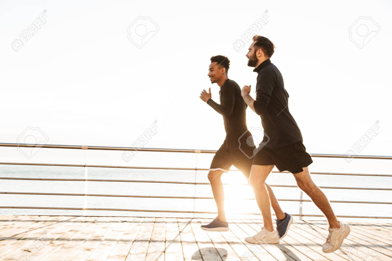 Two attractive confident young healthy sportsmen jogging outdoors at the beach - 130055869