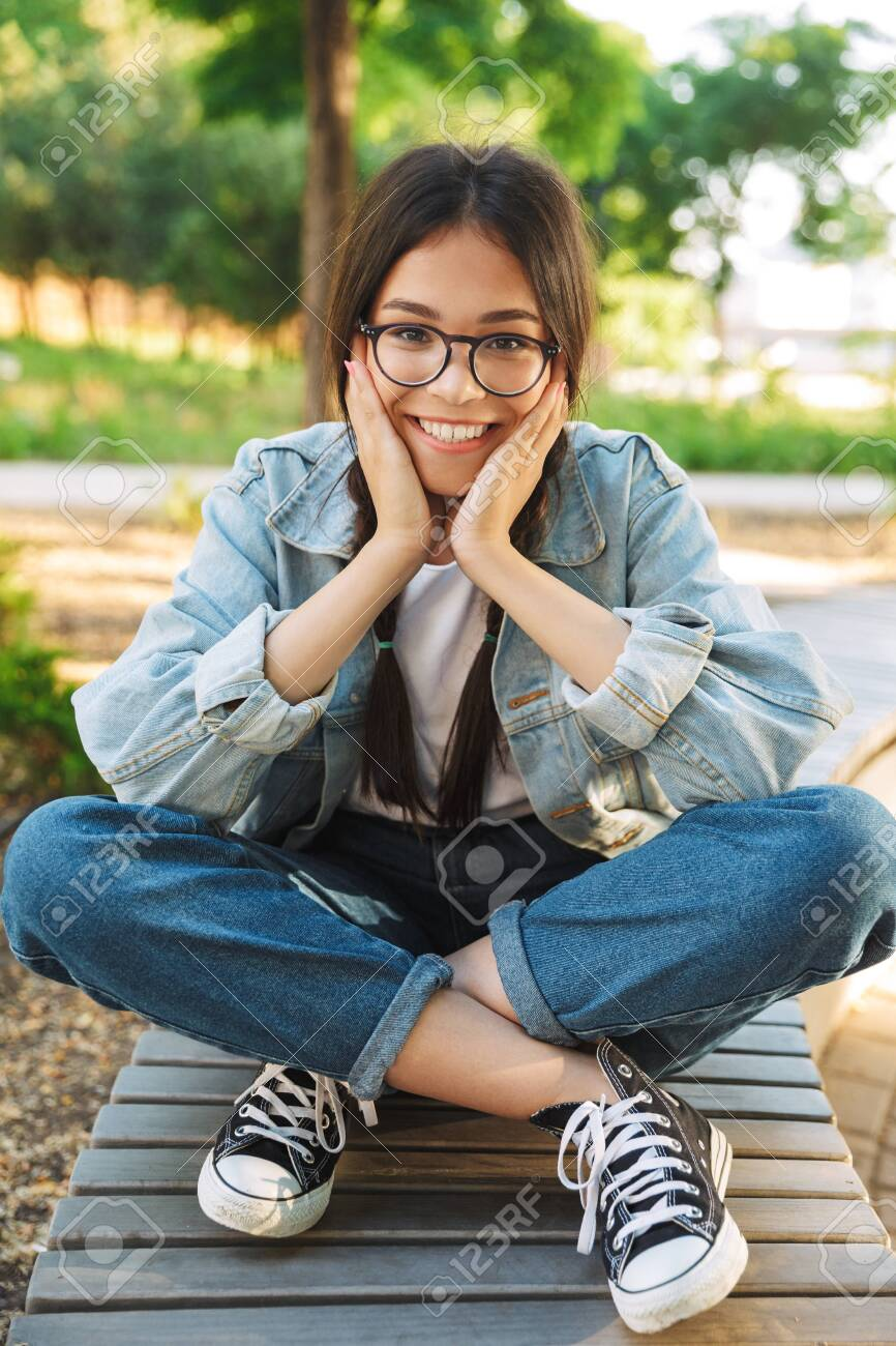 Photo of a pleased happy cute young student girl wearing eyeglasses sitting on bench outdoors in nature park. - 130056802