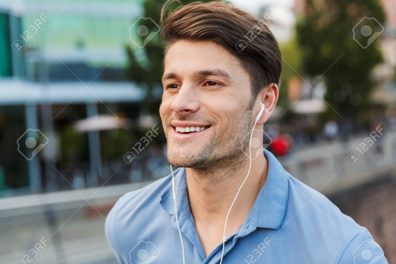 Handsome smiling young man dressed casually spending time outdoors at the city, listening to music with earphones - 129673851
