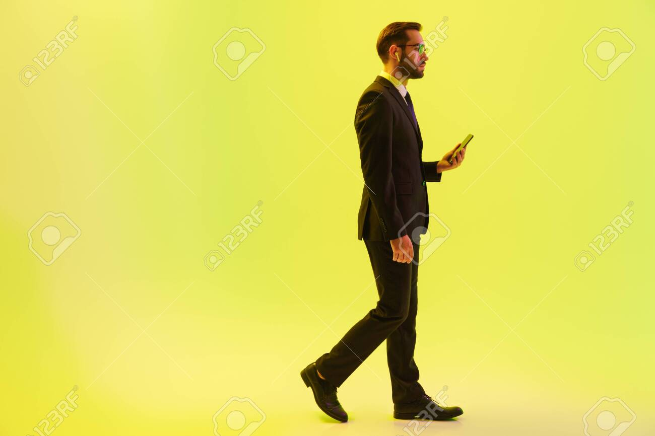 Handsome young businessman wearing formal suit walking isolated over yellow background, using wireless earphones and holding mobile phone - 129805682