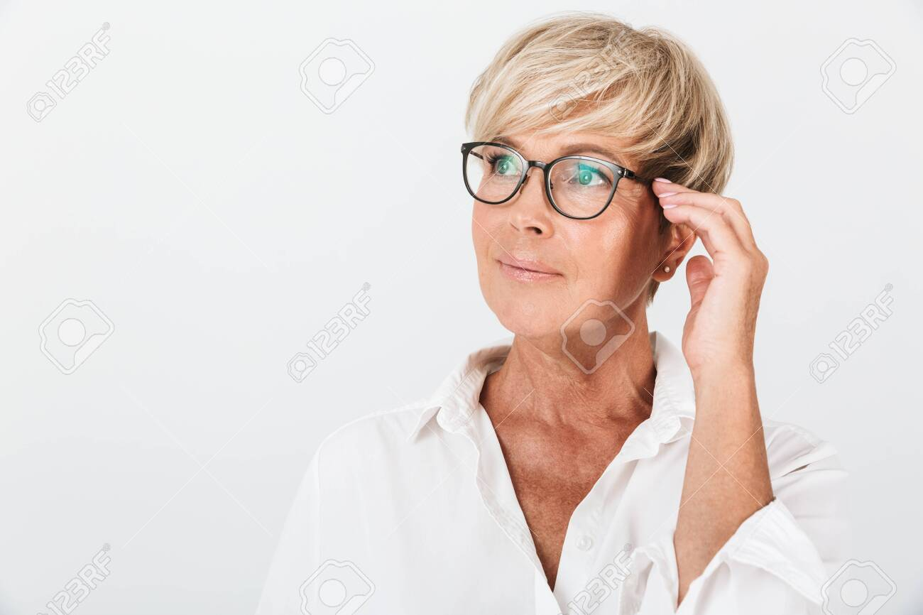 Portrait of beautiful adult woman looking aside and touching her eyeglasses isolated over white background in studio - 130269045