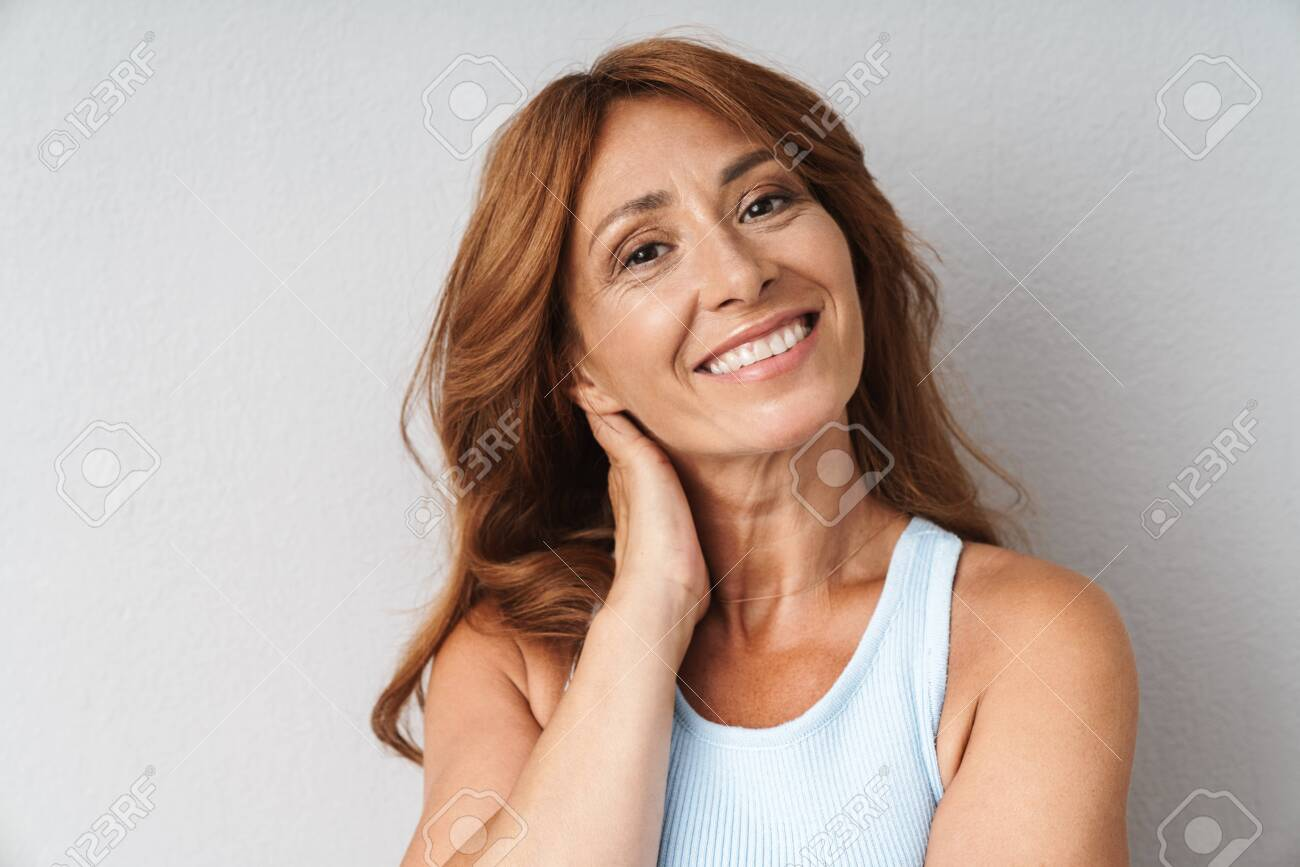 Portrait of an attractive smiling middle aged woman wearing casual outfit standing isolated over beige background, looking at camera - 131926230