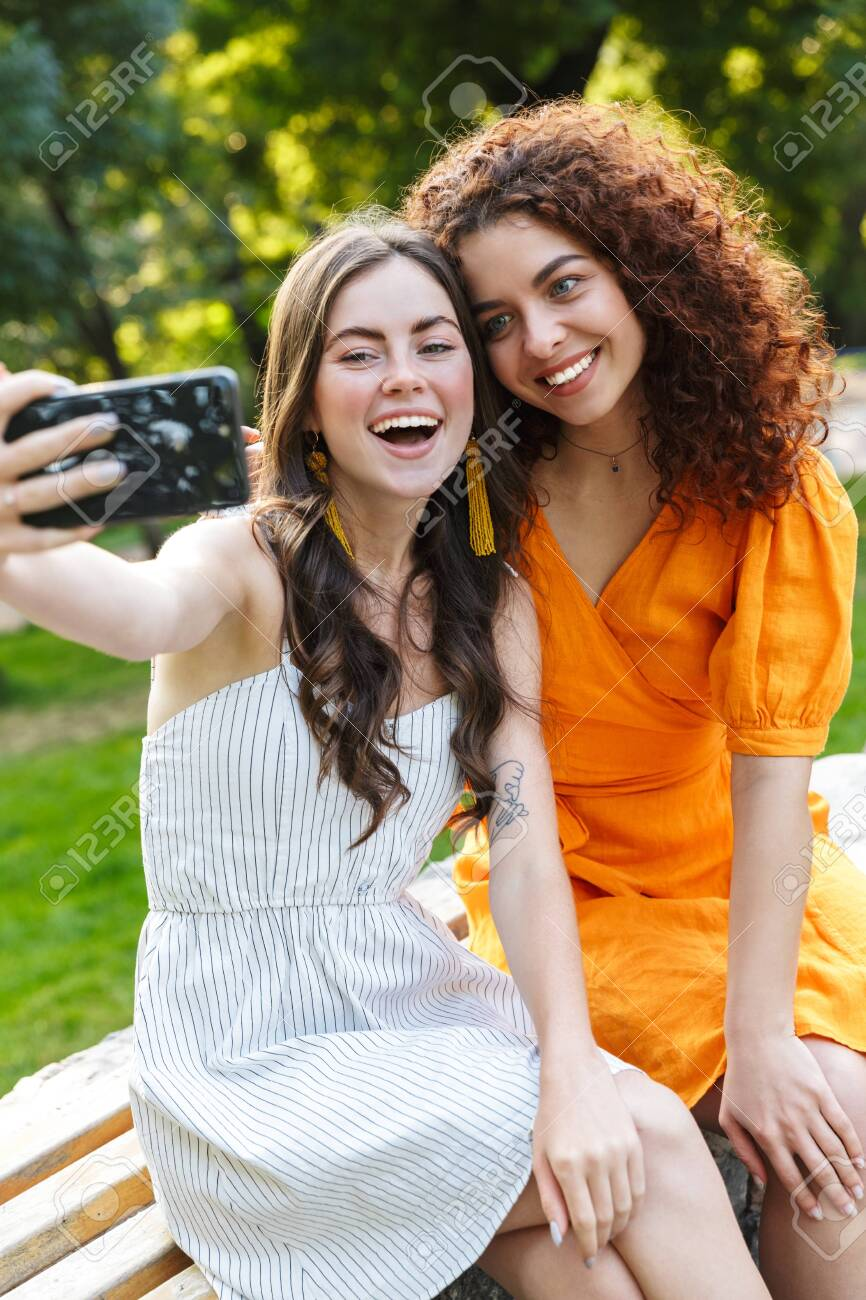 Two cheerful young girls friends wearing summer dresses spending time outdoors at the city park, taking a selfie while sitting on a bench - 134014710