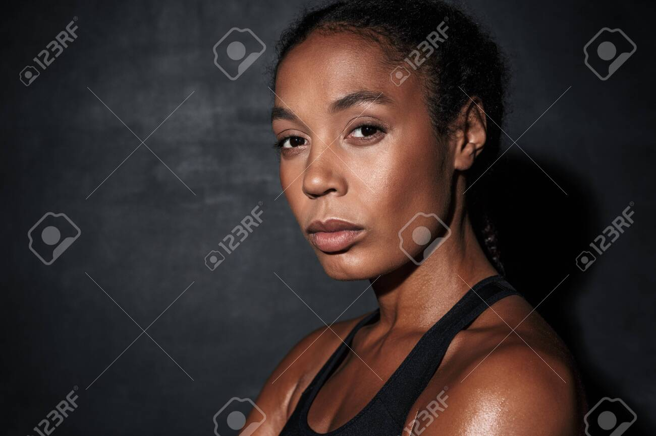 Image closeup of young african american woman in sportswear standing isolated over black background - 134223840