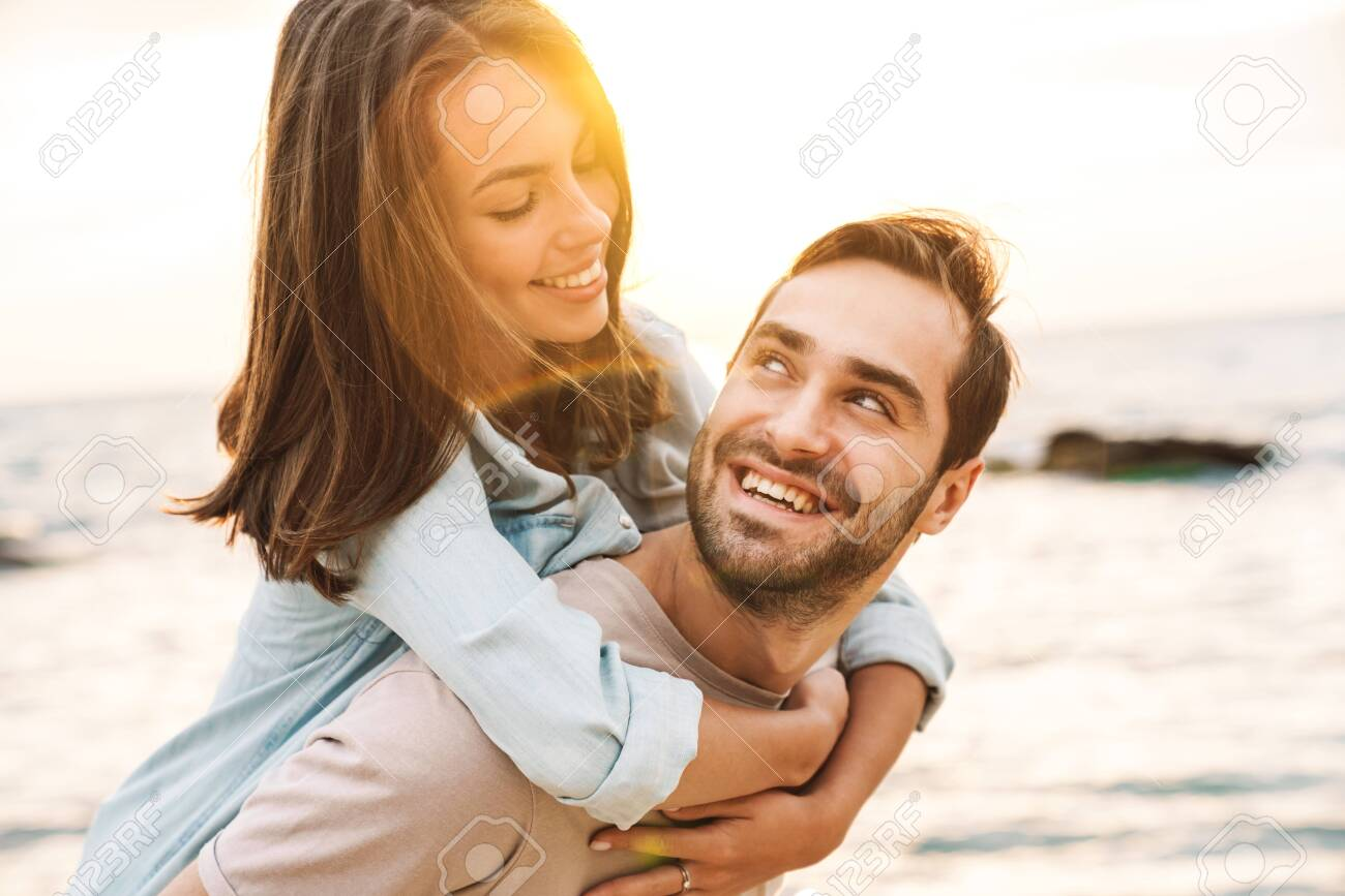Image of young happy man giving piggyback ride and looking at beautiful woman while walking on sunny beach - 135086576