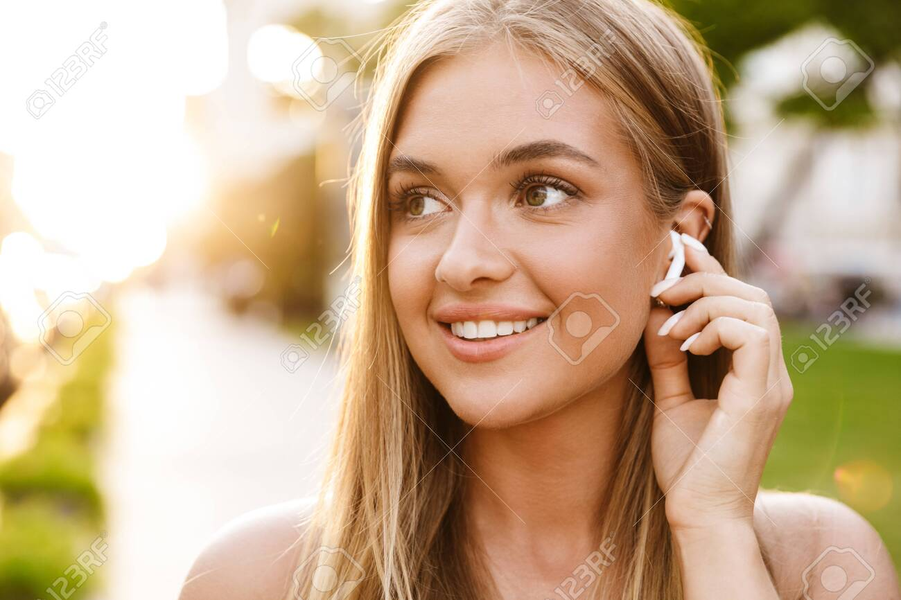 Close up of a smiling beautiful young blonde girl listening to music with earphones while standing outdoors - 135237884