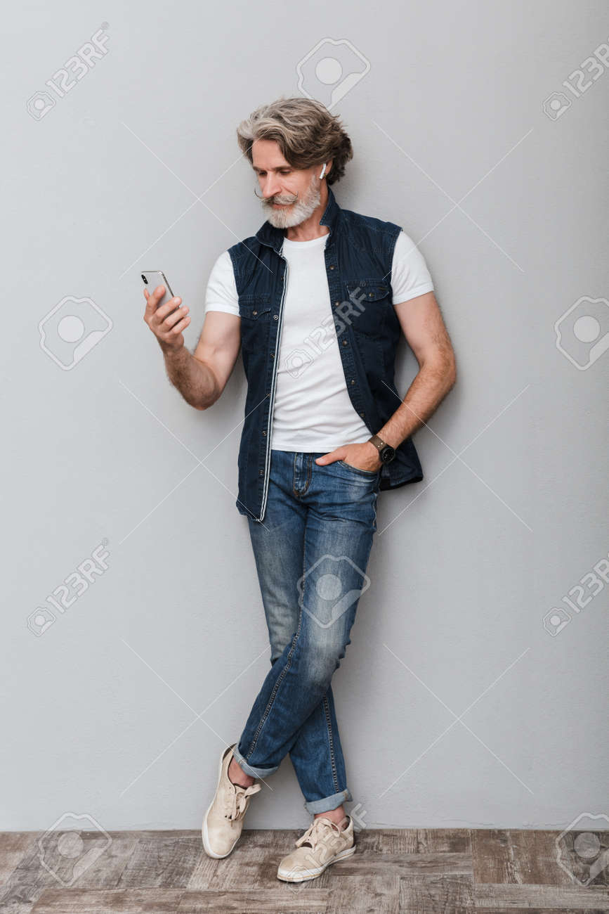 Full length portrait of a handsome smiling stylish mature man wearing a vest standing over gray background, using mobile phone - 137788070