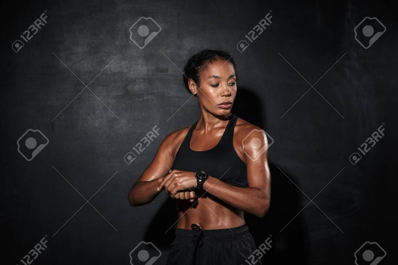 Attractive muscular young african sportswoman standing isolated over black background, checking time - 137938173