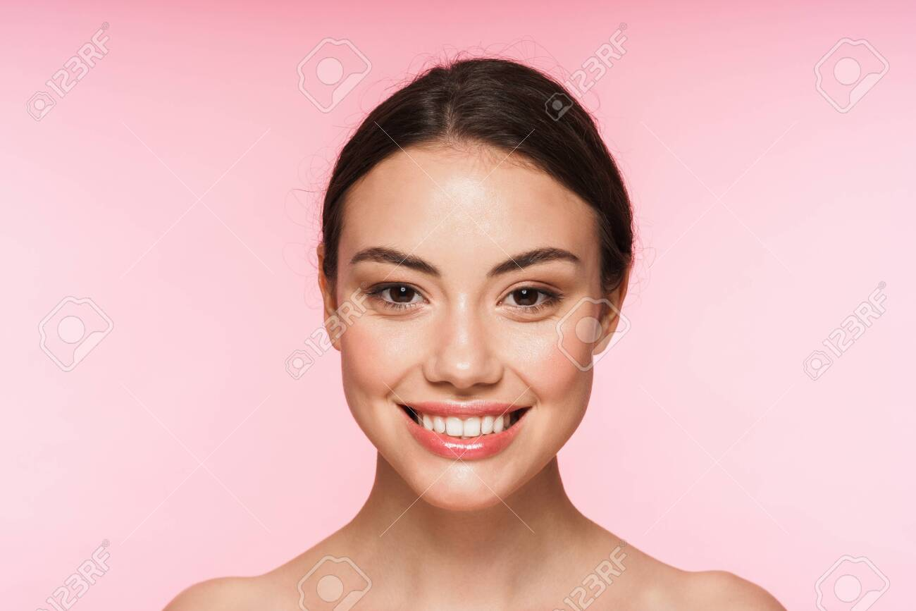 Beauty portrait of a beautiful smiling young brunette woman standing isolated over pink background - 139087799