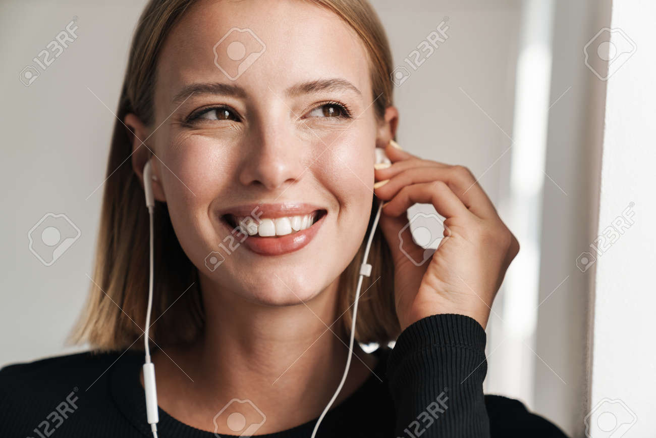 Attractive smiling young blonde short haired woman leaning on a wall while standing indoors, listening to music with earphones - 139088936