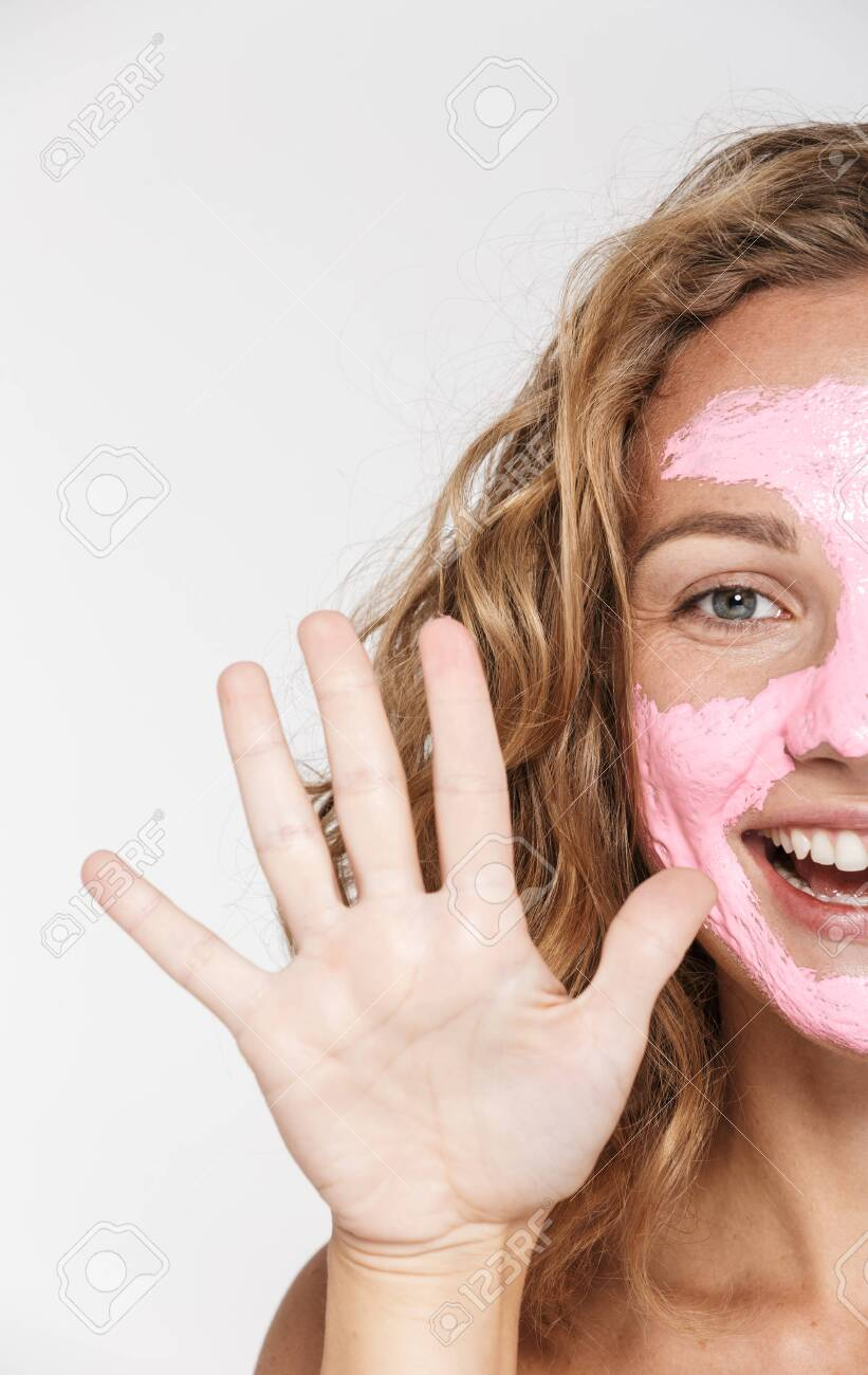 Cropped image of cheerful woman in face mask laughing while showing her palm isolated over white background - 140320494