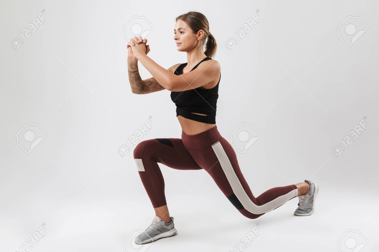 Photo of pretty woman in sportswear stretching her body while doing workout isolated over white background - 142120108