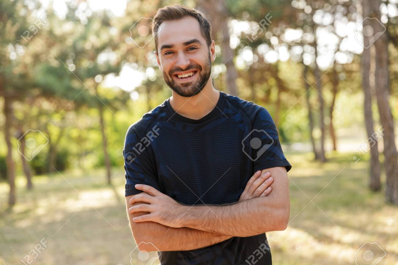 Image of a young strong happy cheery sports man posing outdoors in nature green park looking camera. - 142744663